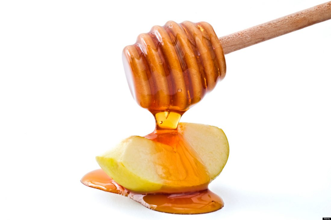 B1XRP1 Honey drippin on a green apple slice isolated on white